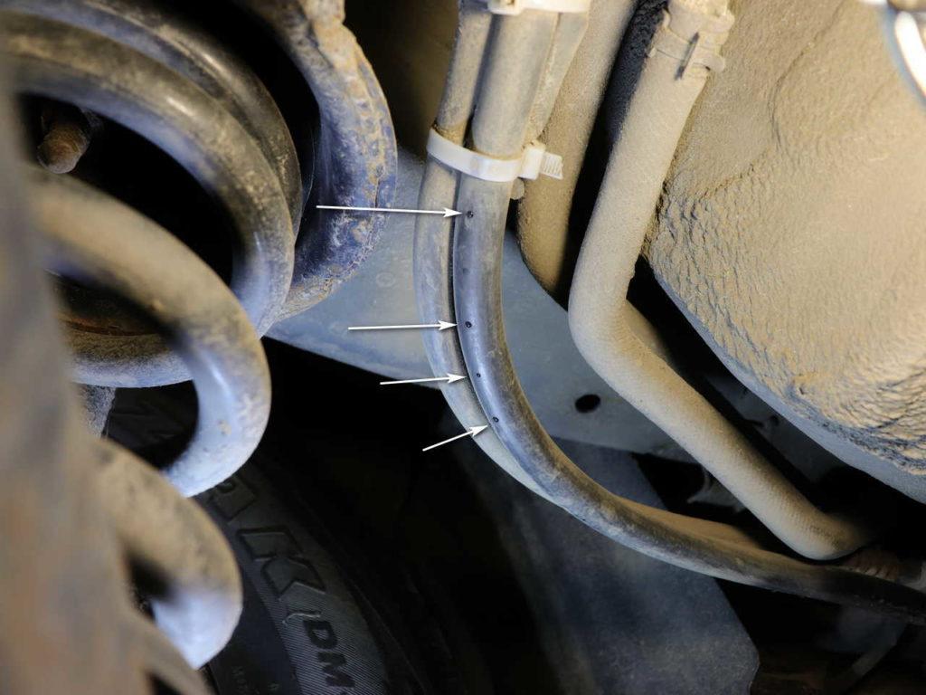 Крупным планом стрелками обозначены места проступания масляных капель на китайских шлангах